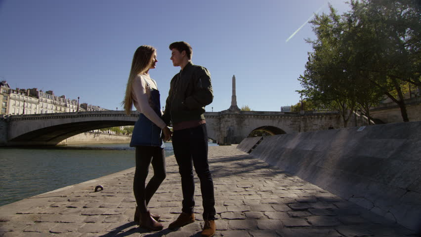 Couple sneak a kiss while taking a walk by the river. Paris, France | Shutterstock HD Video #15686644