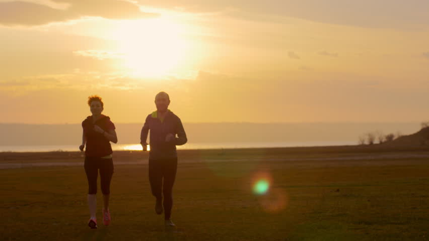 Group of runners training outdoors exercising at sunset in amazing landscape nature. Fit handsome athletic male and female working out for marathon run outside in summer. Couple, man and woman sport. | Shutterstock HD Video #15691834