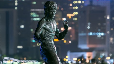 HONG KONG, CHINA - SEPTEMBER 15: Bruce Lee monument timelapse hyperlapse in the night at the Avenue of stars, modern skyscrapers at the background in Hong Kong. Bruce Lee was the most influential. 4K