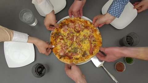 Hands taking pizza cuts from plate on table. Top view. Six unrecognizable people simultaneously spreading arms to get slices of pizza. Group of hungry people and food order eating.