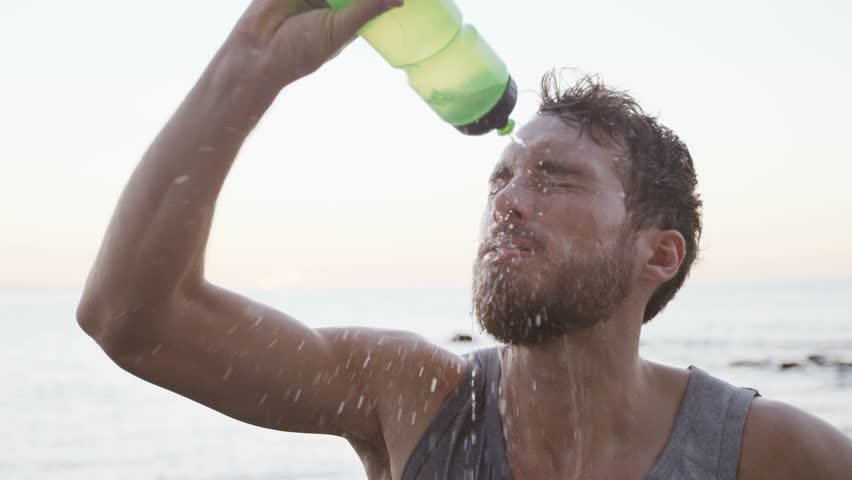 Fitness man drinking water from bottle splashing water in face cooling down after running workout on beach. Thirsty athlete having cold refreshment drink sweating after intense exercise. SLOW MOTION.