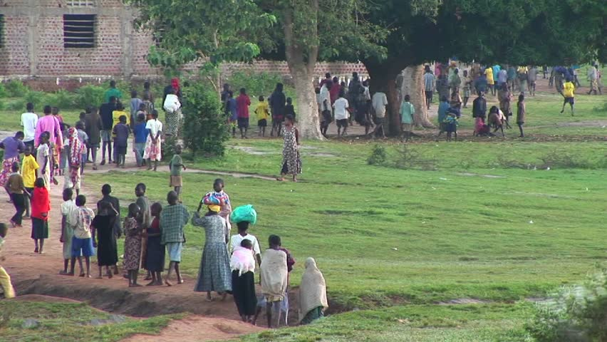 Large group of people walk down a dirt path circa 2009 in Uganda.