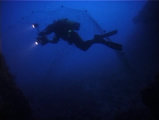 A scuba divers during a wreck. dive. The underwater cameraman stays near a dangerous fishing-net. Shot captured in the Mediterranean Sea (Italy) by 3CCD camcorder - PAL system.  | Shutterstock HD Video #158086