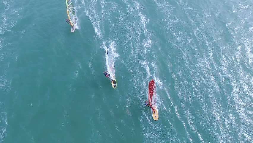 Beautiful aerial view of windsurfers sailing on blue sea. The great wind made for extreme windsurfing racing.