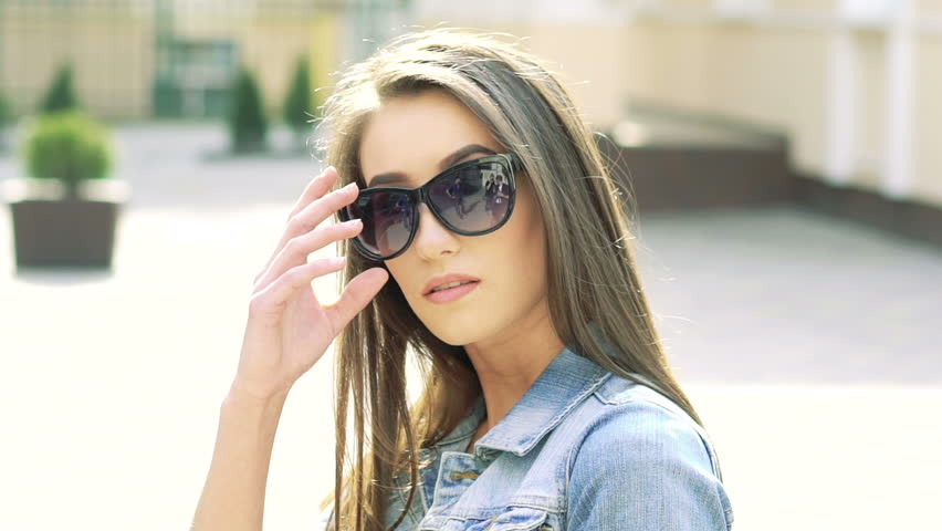 Sexy girl in sunglasses looking on camera on sunshine background. Slowly | Shutterstock HD Video #15827554
