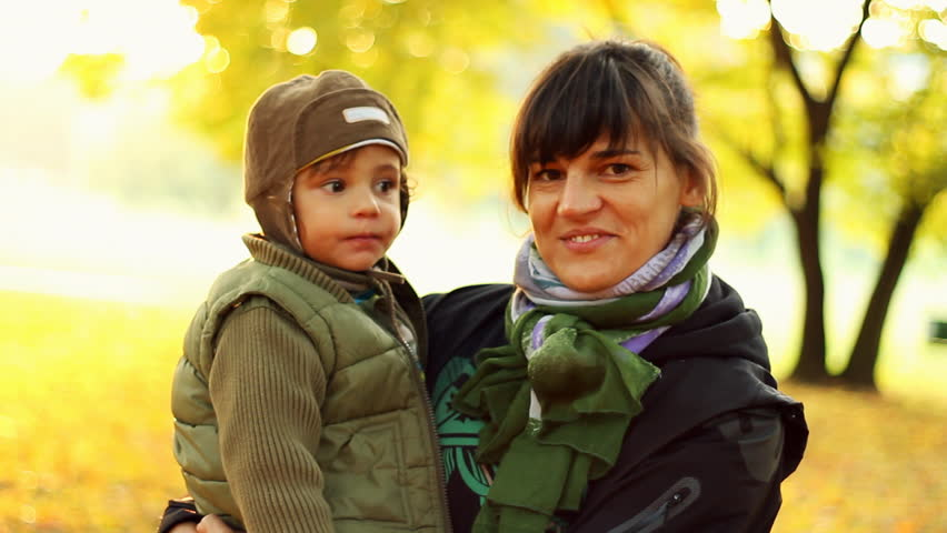 Portrait of happy young mother with her son, outdoors