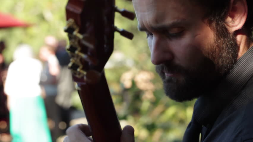 Close-up of man playing acoustic guitar outdoors at a dinner party in northern California. #15847474
