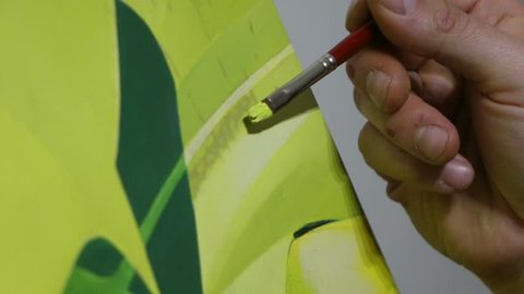 painter finishes framework hand with brush finishes a yellow leaf