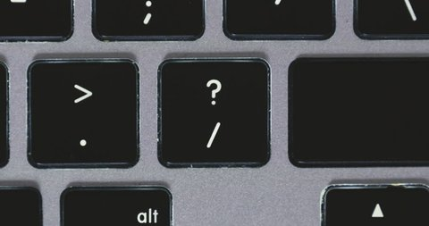 Extreme close up of fingers pressing 'shift question mark' on a keyboard.
