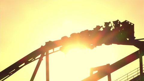 SLOW MOTION CLOSE UP: People riding upside down extreme rail roller coaster attraction in amusement park at golden sunset. Rail looping coaster ride over the setting sun.