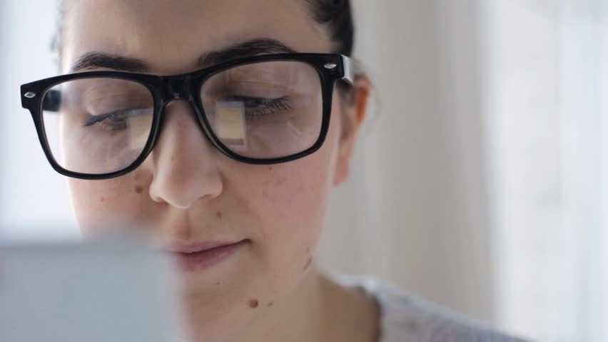 People, technology and leisure concept - young woman in eyeglasses with smartphone at home | Shutterstock HD Video #15880954