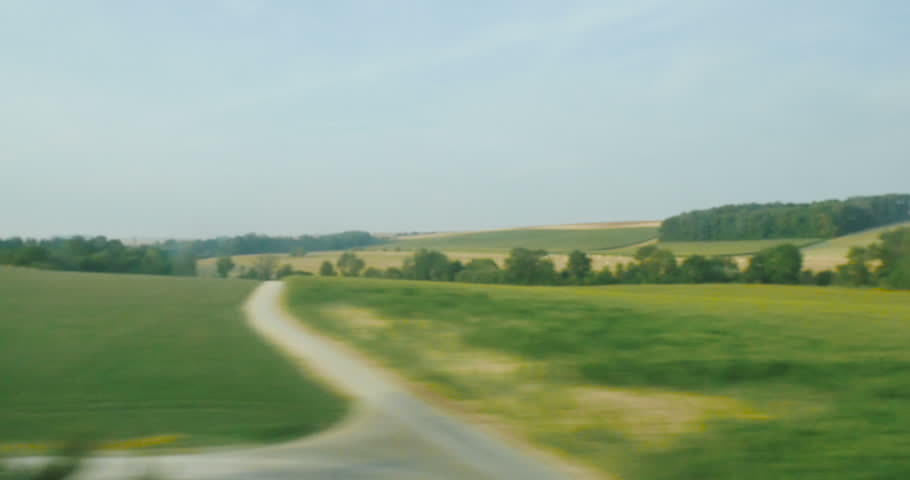 View from the high speed train TGV at beautiful French landscapes with hills and forest