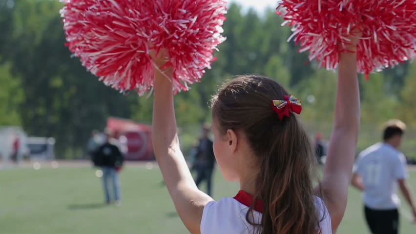 American dancing girl or teenager supports football team. Playing young novice athletes or professional players. Group in white T-shirt and short red skirt. Regular training and love of life. Close up