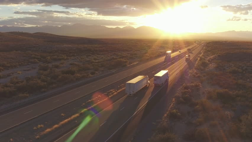 4K AERIAL: Cars and freight semi truck driving on busy highway across the country in beautiful summer evening. People on road trip traveling on busy freeway at golden sunset