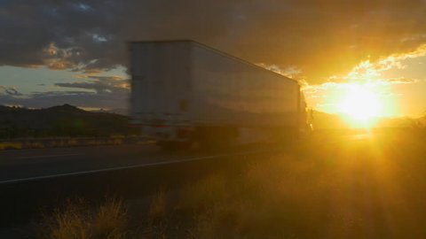 4K CLOSE UP: Freight semi truck speeding on empty highway over golden sun at summer sunset. Transporting truck driving on freeway in sunny morning.