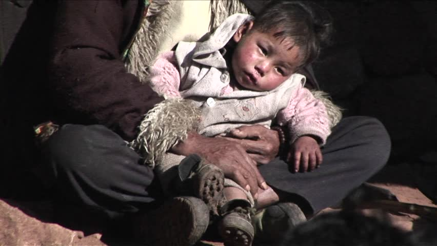 CHINA - CIRCA 2009: A small child sits in a poor beggars arms circa 2009 in China.