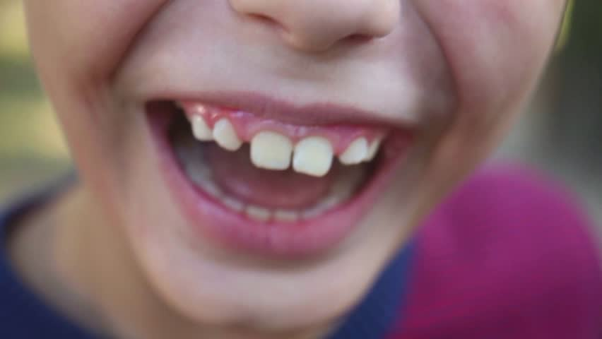 Closeup of cute child mouth smiling and laughing. Real positive emotions of 8 years old boy. Natural lighting. Real time video footage