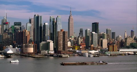 The New York City Skyline on a sunny day.  A barge goes upriver on the Hudson.