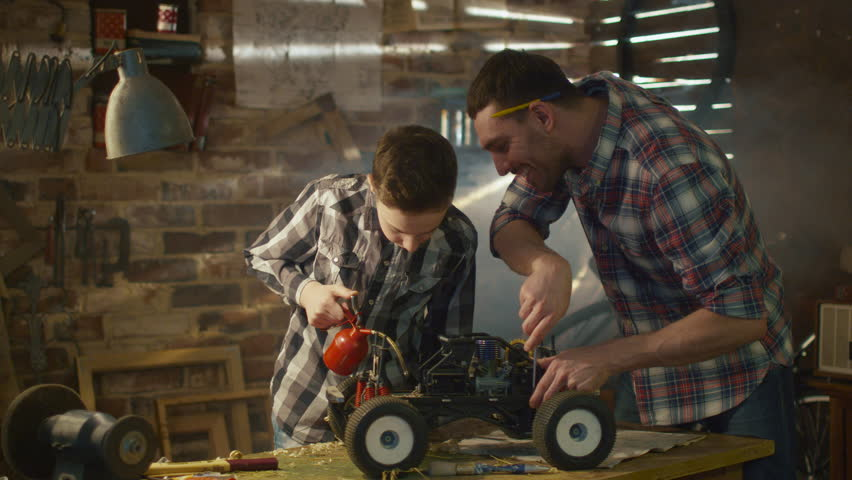 Father and son are working on a radio control toy car in a garage at home. Shot on RED Cinema Camera in 4K (UHD).