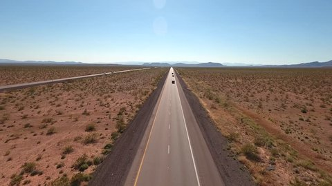 A cool aerial shot of cars and semi trucks driving on I-15 highway in the vast desert near Las Vegas Nevada