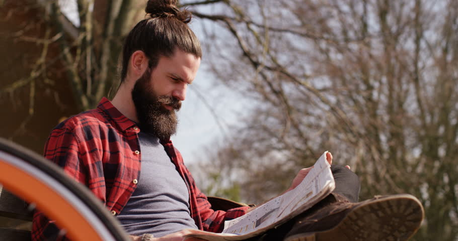 4k, A young man reading a newspaper in a park as he takes a break from cycling. | Shutterstock HD Video #16003684