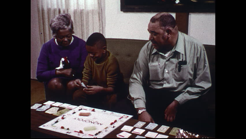 UNITED STATES 1970s: Man and boy play Monopoly/ Woman watches/ Boy opens front door/ Boy throws football