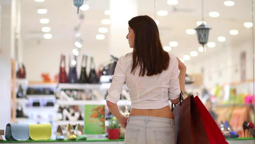 Back of beautiful girl standing with bags near showcase in mall | Shutterstock HD Video #16020988