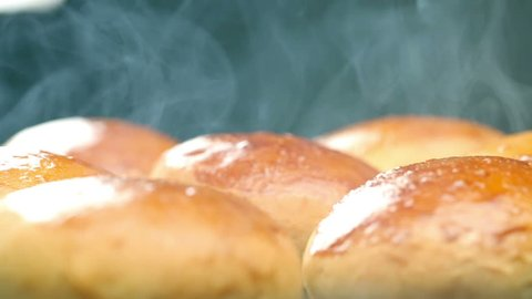 Hot buns for burgers. The hot bread. Fresh pastries. From the hot steaming buns. Wheat bread yellow.