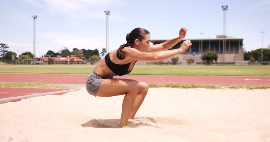 Sportswoman doing long jump landing in sandpit