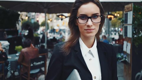 Close-up portrait of young beautiful businesswoman looking at camera with smile outdoors, professional female cafeteria manager wearing glasses and black suit, slow motion