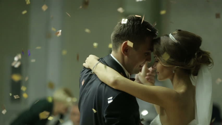 Beautiful brunette bride and handsome groom dancing first dance at the wedding party. Confetti in the air. Very tender moment | Shutterstock Video #16053757