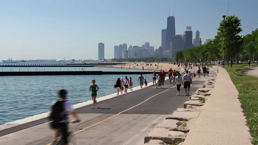 Cyclists and runners enjoying a summer day on the Lakefront path along the Lake Michigan shoreline in Chicago.