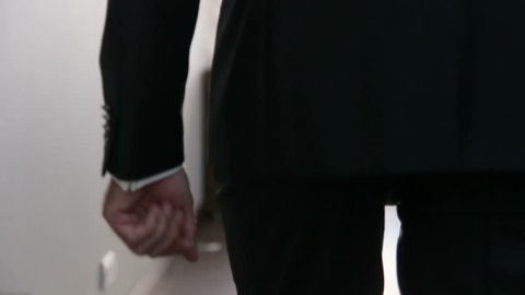 Groom in black wedding suit puts hand into the pocket and walks away. Wedding concept. Slow motion shot