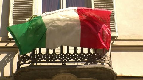 Patriotic Italian flag fluttering from a balcony with white flowers in Turin, Italy