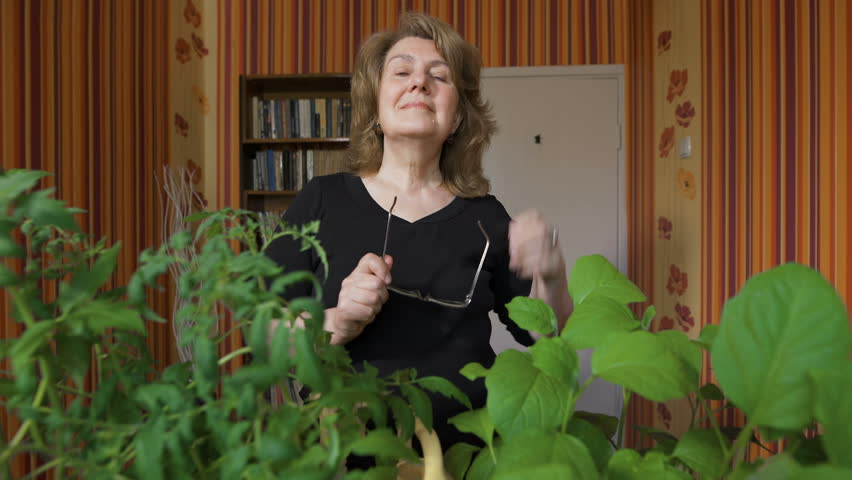 Portrait of a cute old woman at home. It costs about his seedlings, smiling. Her hobby  | Shutterstock HD Video #16115005