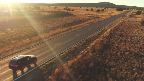 AERIAL: Black SUV car driving along empty country road at golden summer sunset. People traveling, road trip on historic Route 66 through beautiful meadow desert scenery in sunny summer