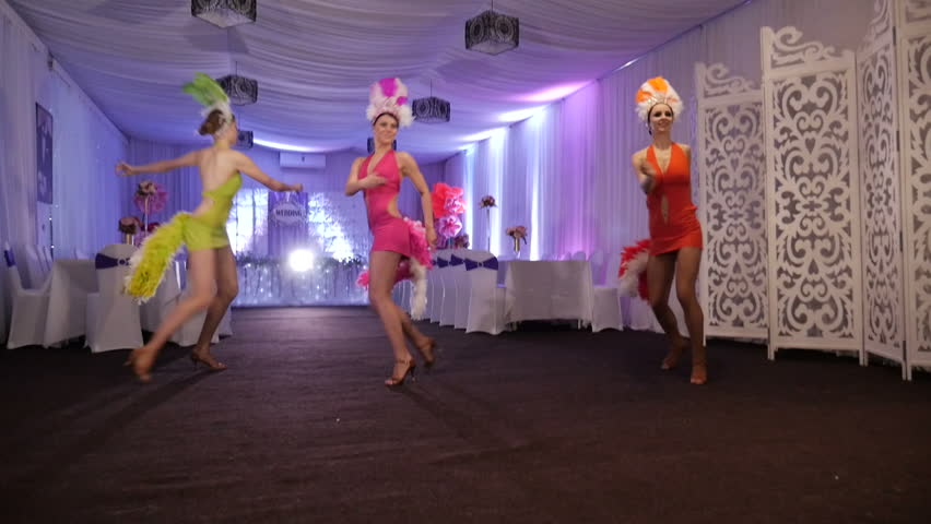 Three beautiful girls dance Latina in White Hall. The costumes of different colors and decorated with feathers. Samba. Dancer latino dance. | Shutterstock HD Video #16122859