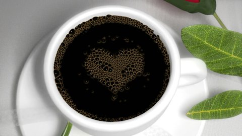 Camera pans over a red rose and lace ribbon and on to a white porcelain cup with Coffee bubbles which pop to reveal a love heart symbol.