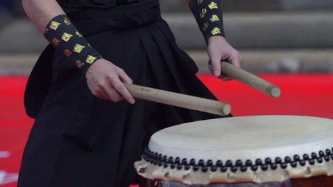Japanese artist is drumming on traditional taiko drums. Drumsticks beating on a traditional drum