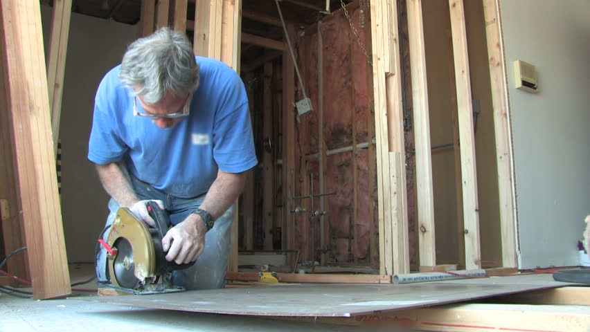 Man uses a power saw to cut wood.