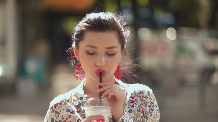 Sexy hot woman drinking shake on sunny day