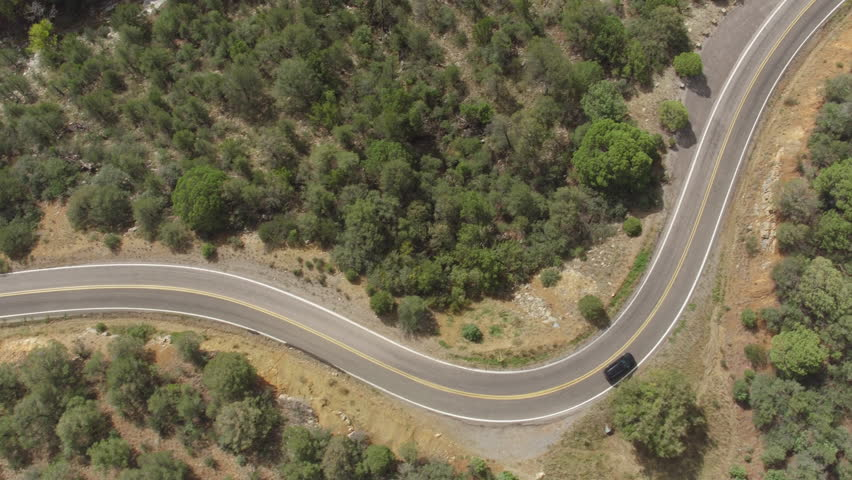 AERIAL: Black SUV jeep car driving along the winding mountain pass road through the forest. People traveling, road trip on curvy road through beautiful countryside scenery in sunny summer | Shutterstock HD Video #16165957