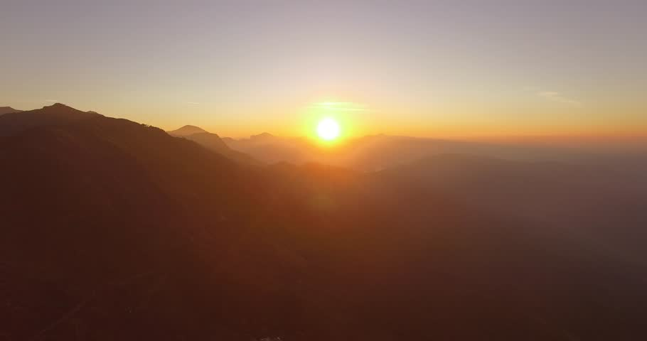 Aerial shot, flying into the sunrise over mountains in Munnar, India