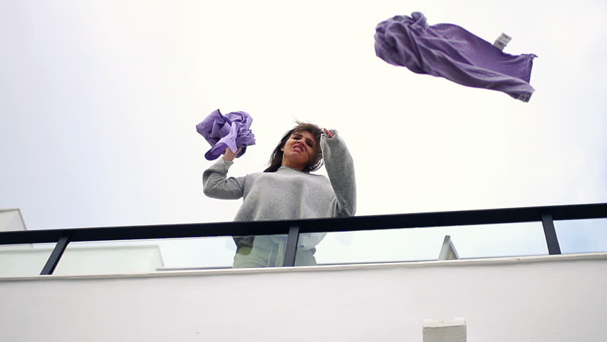 Angry woman throwing out male clothes from terrace, super slow motion 240fps