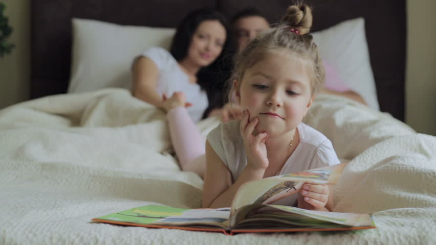 Little girl is reading a book under a blanket with a flashlight in a daughter with family reading a book in bed hd stock video clip sciox Gallery