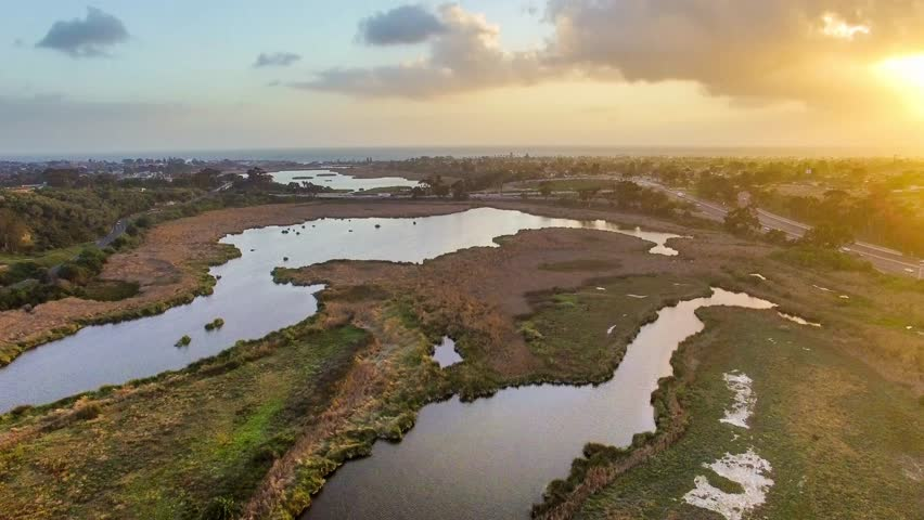 Aerial footage of warm sunset over Buena Vista Lagoon with views of the Southern California coastal cities of Oceanside and Carlsbad, I-5 freeway and Pacific Ocean in distance