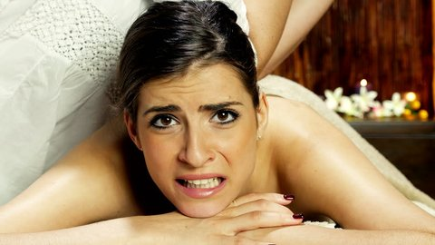 Woman suffering pain during strong massage making funny faces 4K closeup