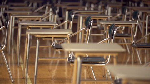 A school gymnasium is filled with desks and vacantly sits, waiting for standardized testing to begin.