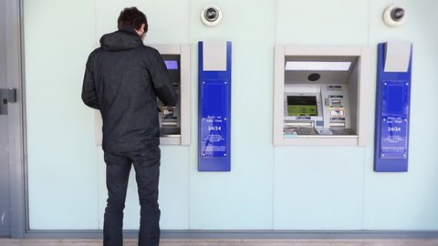 Man Using ATM Bank Machine Outdoors. Automated teller machine is an electronic telecommunications device that enables the customers to perform financial transactions.