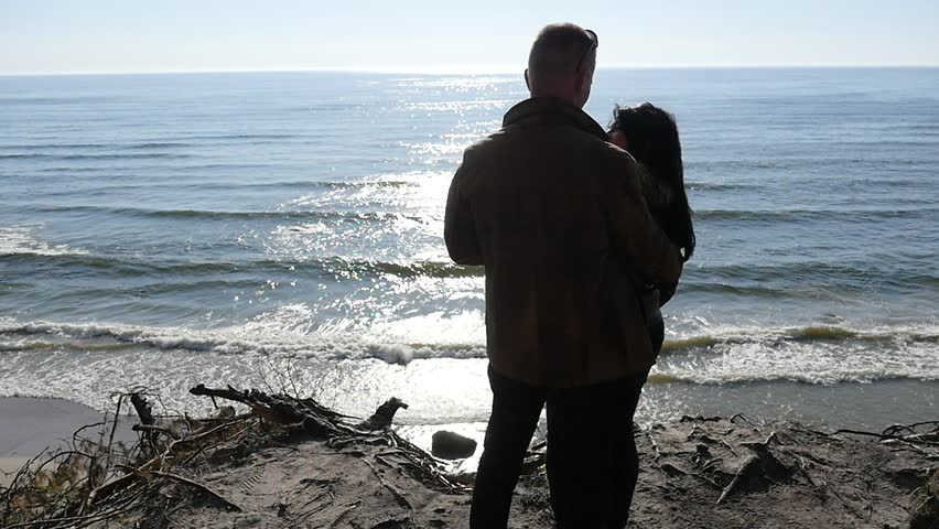 Man kissing woman silhouette against sun - cliff with sea view slow motion